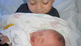 A young boy holding his newborn brother