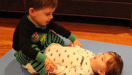A young boy playing with his newborn brother